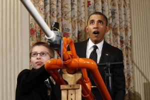 U.S. President Barack Obama reacts as Joey Hudy of Phoenix, Arizona, launches a marshmallow from his Extreme Marshmallow Cannon in the State Dining Room of the White House during the second White House Science Fair in Washington February 7, 2012. The fair celebrates the achievements of student winners of a broad range of science, technology, engineering and math (STEM) competitions from across the country. REUTERS/Kevin Lamarque (UNITED STATES - Tags: POLITICS EDUCATION SOCIETY SCIENCE TECHNOLOGY) - RTR2XGJS